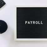 payroll sign board and calculator on white backgro AUG4PHM